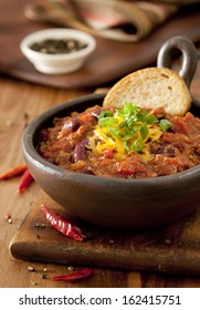 Closeup of a bowl of chili con carne topped with cheese and green onions.