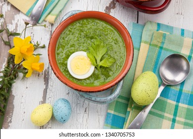 Closeup of bowl of green gazpacho soup with boiled eggs - appetizer for Easter brunch. Easter eggs and flowers.