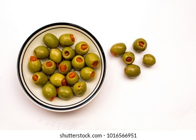 Closeup of a Bowl of Green Stuffed Olives on a white background