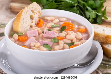 Closeup of a bowl of ham and bean soup with carrots and sliced french bread