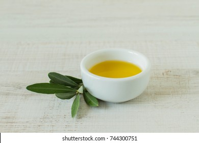 Close-up of bowl with olive oil and olive branch kept on wooden table
