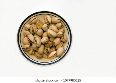 Closeup of a Bowl of Pistachio Nuts on a White Background