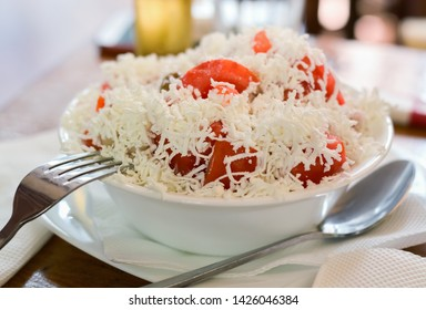 Closeup of a bowl with salad of chopped tomato and white cheese