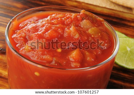 Closeup of a bowl of salsa with lime on the side