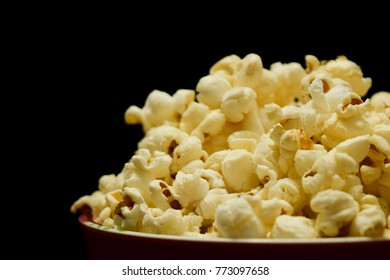 Closeup of a bowl of salted butter popcorn with black background
