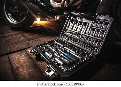 Close-up of a box with tools lies on the wooden floor against the backdrop of a motorcycle - Shutterstock ID 1803193057