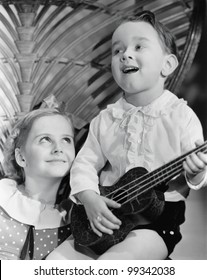 Close-up of a boy playing a guitar with his sister