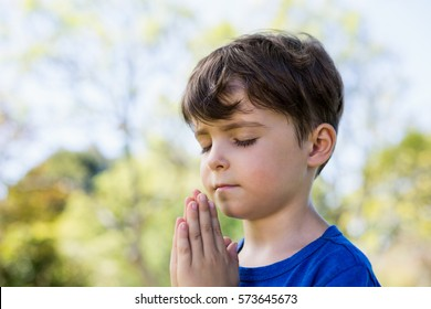 Close-up of boy praying with eyes closed in park
