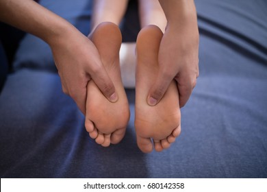 Close-up of boy receiving foot massage from female therapist on bed at hospital ward