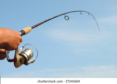 Closeup of a boys hand holding a fishing rod and reel