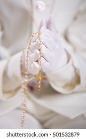 Closeup of a boy's hands with white gloves holding a gold rosary for his First Holy Communion. Shallow depth of field.