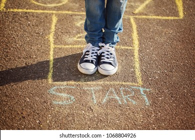Closeup of boy's legs and playing hopscotch on playground outdoors. Hopscotch popular street game.