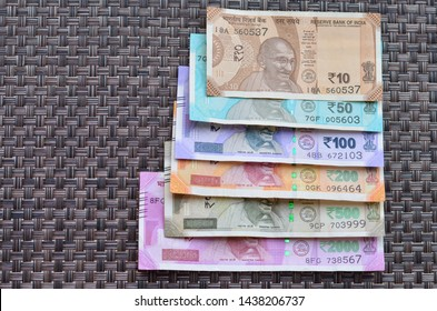Closeup of brand new colorful Indian currency bank notes of 10, 50,100, 200, 500 and 2000 rupees bundle issued and in circulation after demonetisation against brown background