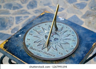 Close-up of a brass sundial mounted on a stone plinth in a garden, Sundial in the Summer sun.