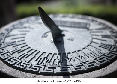Close-up of a brass sundial mounted on a stone plinth in a garden. Soft selective focus and shallow depth of field.