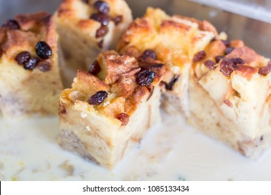 Close-up Bread pudding with raisins on white cream.