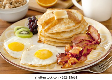 Closeup of a breakfast plate with pancakes, eggs, bacon and fruit.