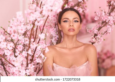 Closeup breast up portrait of elegant beautiful woman with makeup and pony tail hair in evening dress. Fashionable photo in pink colors