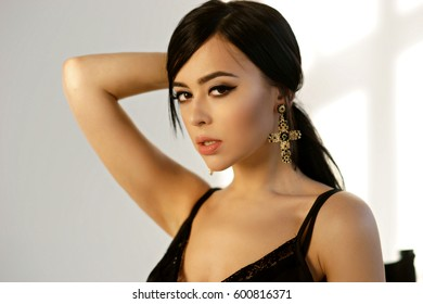 Closeup breast portrait of young beautiful brunette woman with long straight hair. Pretty girl wearing necklace, earrings and ring with diamonds against white wall with geometrical shadows