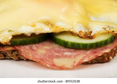 Closeup of a bred with salami and fried eggs with cheese
