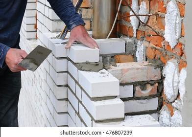 A closeup of a bricklayer worker installing white blocks and caulking brick masonry joints exterior wall with trowel putty knife outdoor.