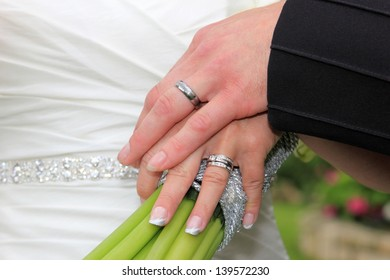 closeup of a bride and groom hands with wedding rings