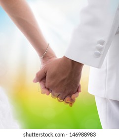 Closeup of  bride and groom holding hands isolated on white background