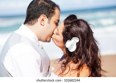 closeup of bride and groom kissing on beach
