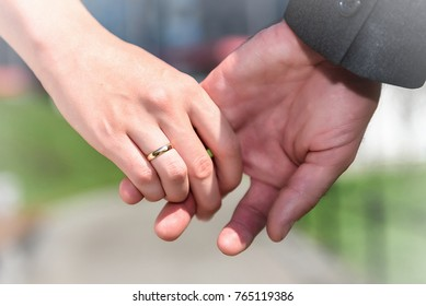 Closeup of bride and groom showing wedding rings touching hands.