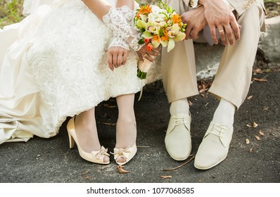 Closeup of bride and groom sitting together outdoors. Horizontal color photography.
