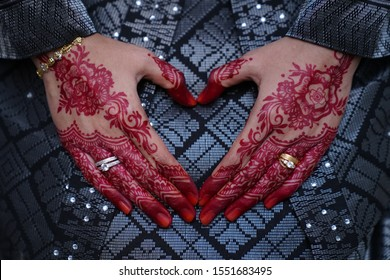 Close-up of bride hand heart sign with mehndi henna tattoo and two wedding rings.