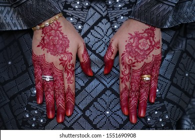 Close-up of bride hand with red henna and wedding rings.