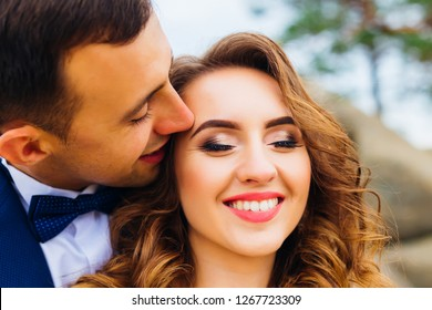 Close-up of a bride with a make-up that looks down. man hugs his woman