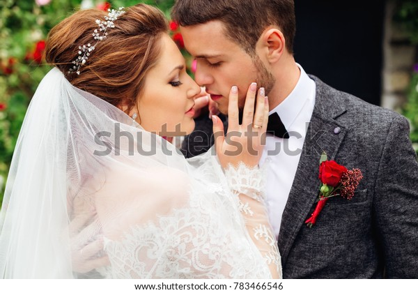 a close-up of the bride that touches the groom face between them the passion flares up