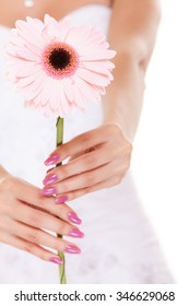 Closeup of bride in white wedding dress giving pink gerbera daisy flower. Young woman girl isolated on white background.