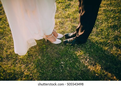Closeup of bride's and groom's feet and shoes
