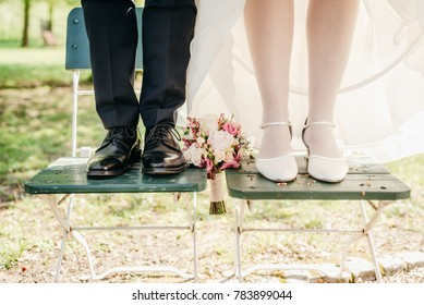 Closeup of brides and grooms feet standing on a chair with bridal bouquet between