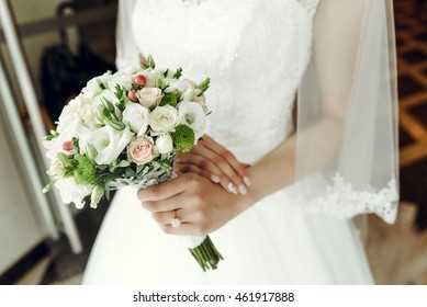 Closeup of bride's hand holding white wedding bouquet