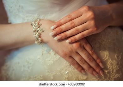 A closeup of bride's hands in pearl bracelet