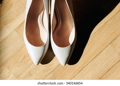 close-up of a bride's shoes on a wooden floor. The scene is illuminated by natural sunlight.