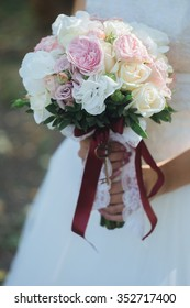 Closeup of Bride's Wedding Bouquet at the Bride is holding two hands red wedding bouquet of fresh real flowerssummer day
