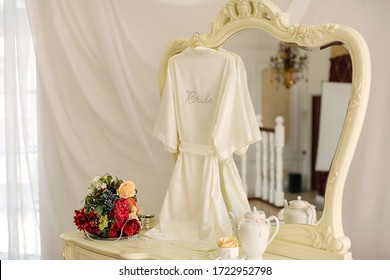close-up of the bride's white silk robe with an inscription of rhinestones hanging on a curly mirror.Women's dressing table.There is a white teapot,a bright bouquet. Morning of the bride wedding day.