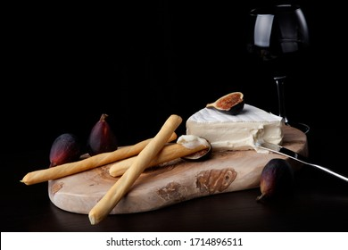 Closeup of Brie cheese with breadsticks, fresh black figs and glass of red wine - great snack for wine tasting. Over black background. Contemporary appetizers series.