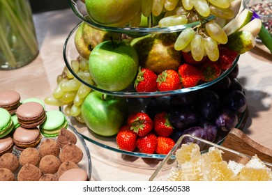 Closeup bright fresh fruits: apples, strawberry, pear, grape, honeycombs cubes in glass bowl, flowers irises, macaroons, truffles on buffet table. Concept dessert table at birthday in caffee