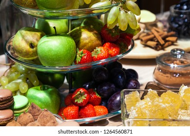 Closeup bright fresh fruits: apples, strawberry, pear, grape, honeycombs cubes in glass bowl, flowers irises, macaroons, truffles on buffet table. Concept dessert table at birthday in restaurant
