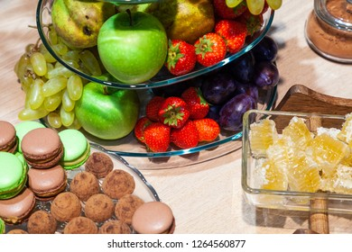 Closeup bright fresh fruits: apples, strawberry, pear, grape, honeycombs cubes in glass bowl, flowers irises, macaroons, truffles on buffet table. Concept dessert table at birthday in house
