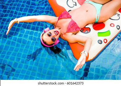 Closeup of a bright funny happy woman, floating on an inflatable pizza in the pool, fashionable bikini, sunglasses, pink headphones, trendy accessories laughing, going crazy, emotions. view from above