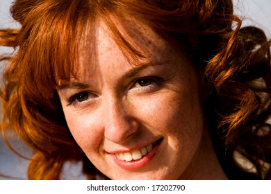 Close-up bright portrait of red-haired lovely young woman outdoors