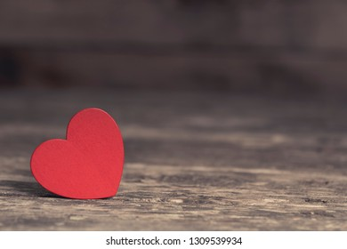 Closeup of bright red heart-shaped decorative element in ray of sunlight on wooden table