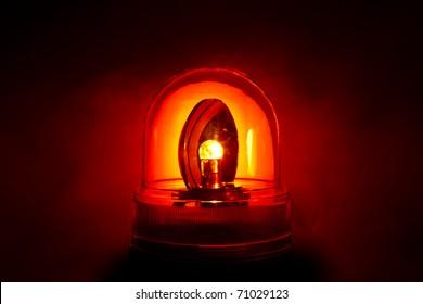 Closeup of a bright red police light shot through a smoky night